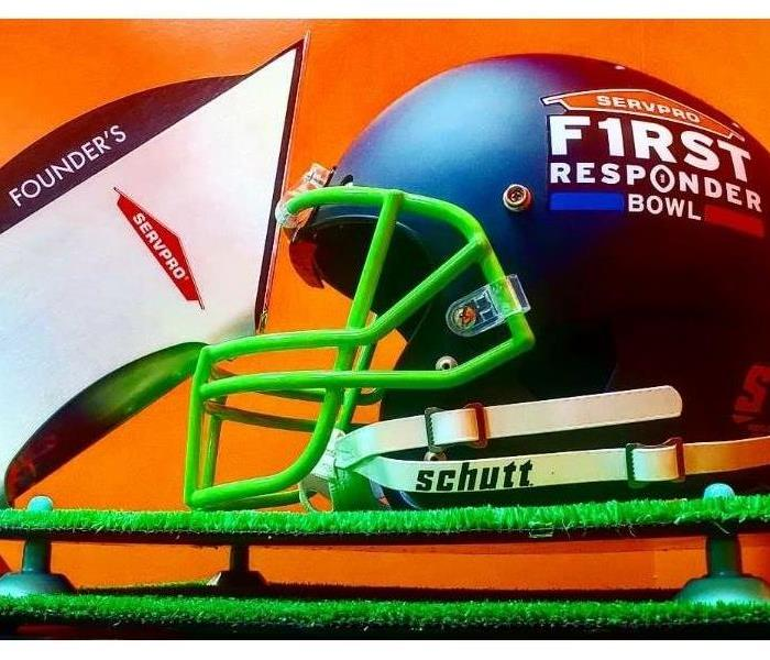 An award and football helmet in front of an orange background.