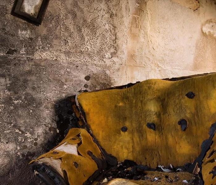 Yellow chair in a room, room and chair have fire and soot damage. Walling has damage as well.