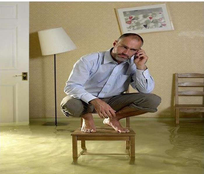 Man squatting on chair in room with water rising